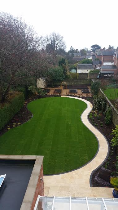 An Indian Sandstone patio with gravel pathways, planting and a hand built  archway